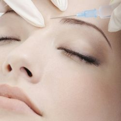 cosmetic injection of botox to the pretty female face - close-up portrait